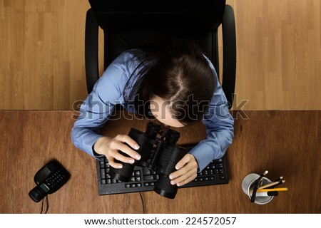 woman at her desk looking through binoculars, taken from a birds eye view - stock photo