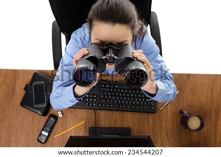 woman at hers desk looking through binoculars shot from a birds eye view - stock photo
