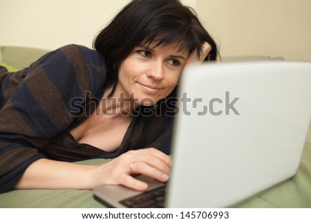 Woman at home lying on sofa and working with laptop - stock photo