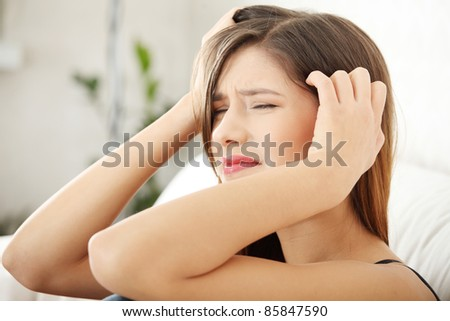 Woman at home with terrible headache or big problem - stock photo