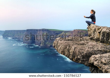 Woman at meditation on the edge of cliff - stock photo