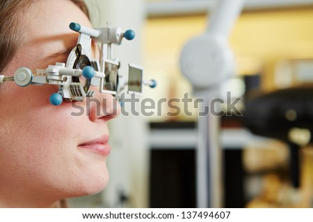 Woman at optician with trial frame and trial glasses for lens determination - stock photo