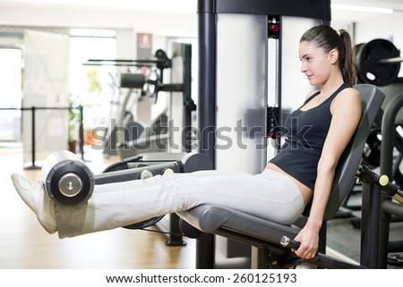 Woman at quadriceps exercise pull machine - stock photo