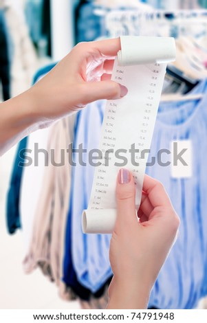 woman at shop holds in her hands roll of paper with printed receipt - stock photo