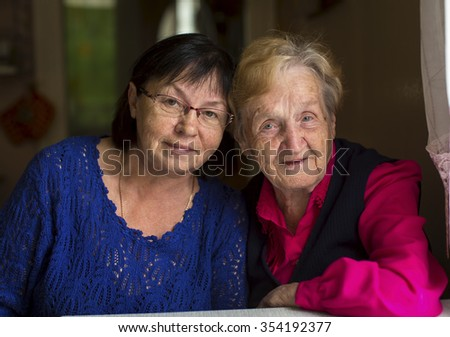 Woman at the age with his old mother. - stock photo