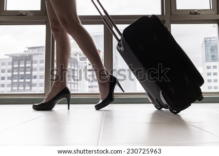 Woman at the airport with suitcase - stock photo