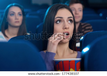 Woman at the cinema. Attractive young woman eating popcorn and watching movie while sitting at the cinema  - stock photo