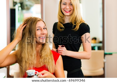 Woman at the hairdresser getting advise on her hair styling, the girls are drinking Cappuccino - stock photo