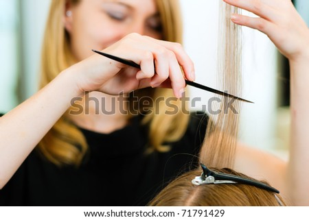 Woman at the hairdresser, she is cutting - close-up with selective focus on her hands - stock photo