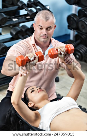 Woman at the health club with personal trainer, learning the correct form with barbell - stock photo