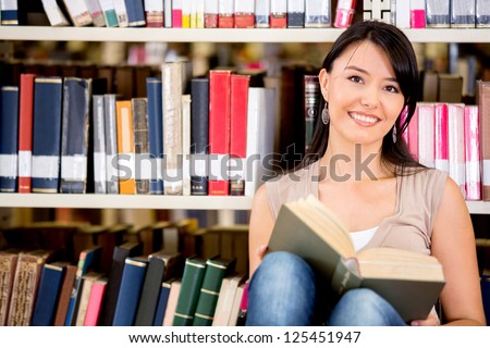 Woman at the library reading a book - stock photo