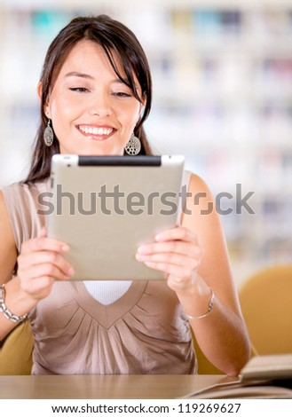 Woman at the library reading a book on an e-reader - stock photo