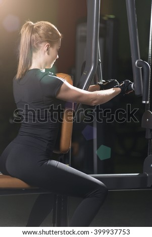 Woman at the sport gym doing arms exercises on a machine - stock photo