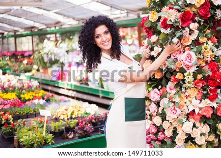 Woman at work in a colorful greenhouse - stock photo
