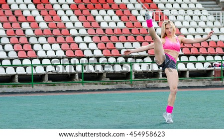 Woman athlete on the stadium. Fitness-woman make exercises. - stock photo