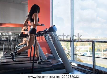 Woman athlete running on treadmill - stock photo