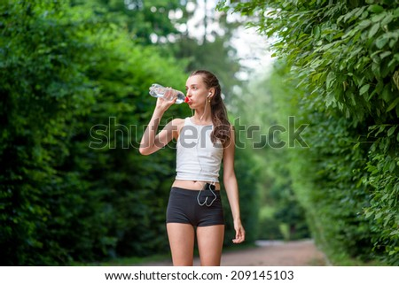 Woman athlete takes a break. Drinking water, out on a run in the park - stock photo