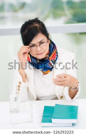 Woman attentively looking at meds - stock photo
