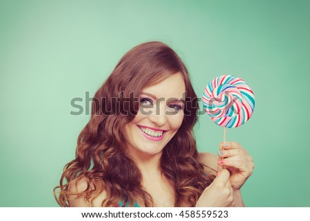 Woman attractive cheerful girl holding colorful lollipop candy in hand. Sweet food and enjoying concept. Studio shot green blue background, toned image - stock photo