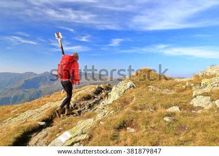 Woman backpacker walking a sunny trail across the mountains - stock photo