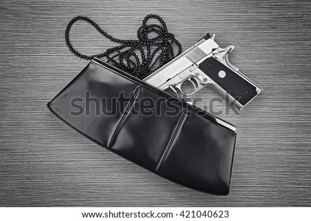Woman bag with gun hidden, Handgun and accessories falling from a woman's purse. (Black & White) - stock photo