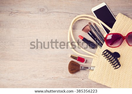 Woman bag with makeup and fashion objects. View from above - stock photo
