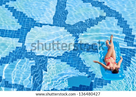 Woman bakes on inflatable mattress in pool with wind rose image at bottom - stock photo