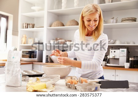 Woman baking at home following recipe on a tablet - stock photo