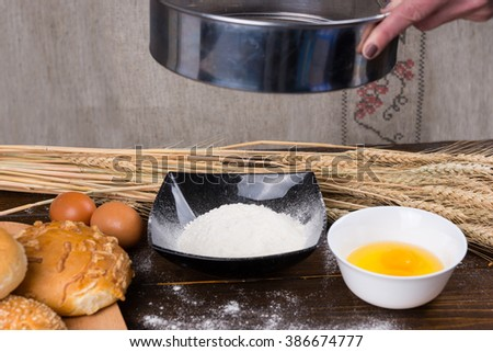 Woman baking fresh bread rolls holding an oven pan above bowls containing eggs and flour with assorted rolls to the side - stock photo