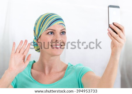 woman, bald from chemotherapy, doing a selfie with cell phone   - stock photo