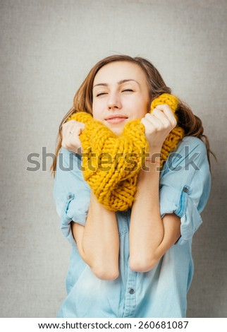Woman basking cold scarf. isolated on gray background - stock photo