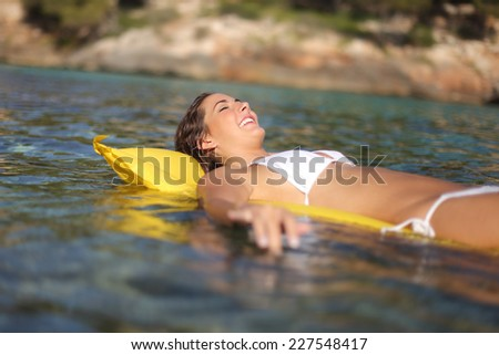 Woman bathing on an inflatable bed on the beach on summer vacations - stock photo