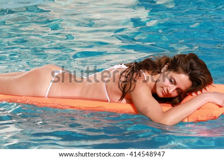 Woman bathing on inflatable mattress in the pool - stock photo