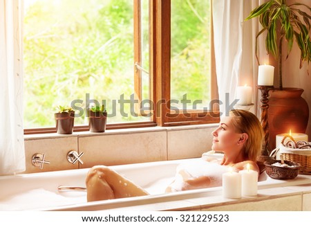 Woman bathing with pleasure, lying down in the tub with foam and looking in the window, spending time in luxury spa resort - stock photo