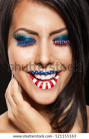 Woman beautiful face with perfect makeup. on the lips and eyes painted an American flag - stock photo