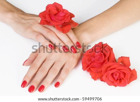 Woman beautiful hands with red manicure and scarlet roses - stock photo