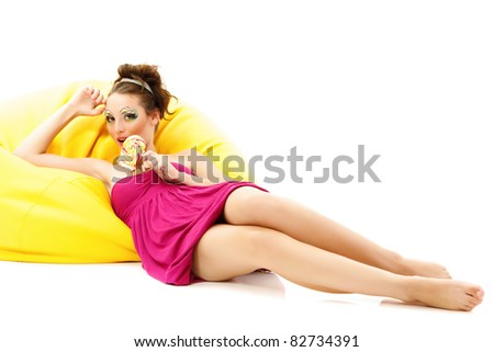 woman beautiful make-up young licks candy on yellow sofa isolated on white background - stock photo