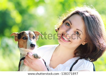 woman beautiful young happy with dark hair in striped sweater holding small dog Jack Russell Terrier - stock photo