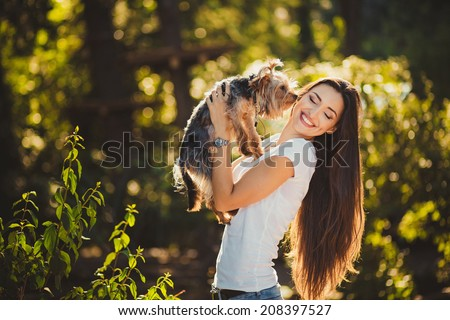 Woman beautiful young happy with long dark hair holding small dog - stock photo