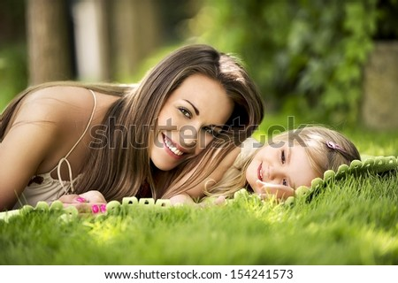 woman beautiful young woman with a daughter on the lawn in the garden - stock photo
