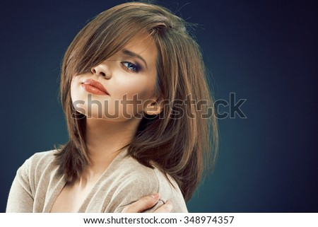 Woman beauty face against dark studio background. Close up - stock photo