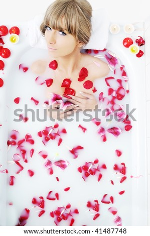 woman beauty spa and wellness treatment with red flower petals in bath with milk - stock photo