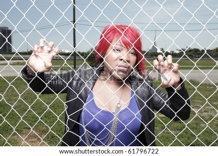 Woman behind a chainlink fence - stock photo