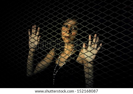 Woman behind a metal fence - stock photo