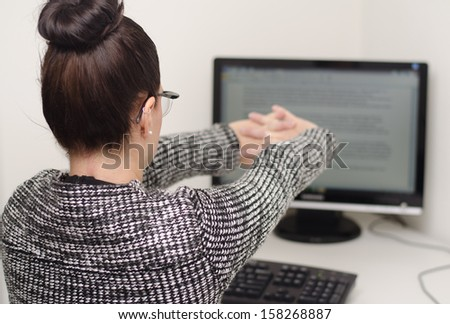 woman behind desk stretching her arms - stock photo