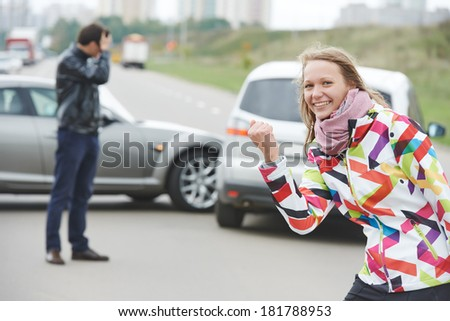 Woman behind steering wheel. Happy unguilty female driver after car crash accident collision in city - stock photo