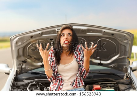 Woman being very angry because of her car's failed engine - stock photo