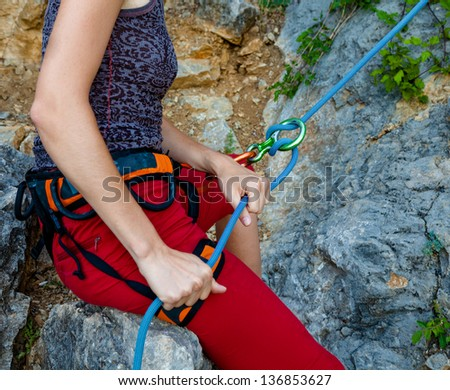 Woman belays climber in mountain closeup - stock photo