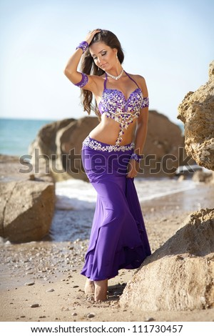 woman belly dancer on sea beach. dancing beautiful slim girl. sexy arabian turkish oriental professional artist in carnival violet costume and diamond jewelry outdoor. exotic bellydance star. Series - stock photo