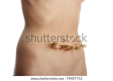Woman belly with clothespin. Slim or fat - stock photo
